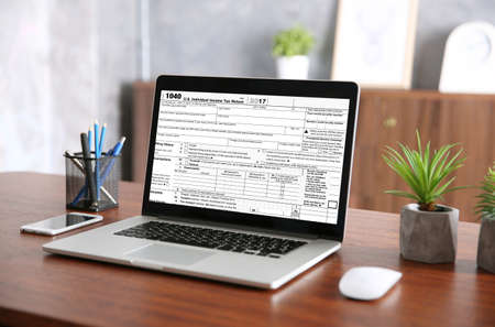 Workplace with office stationery. Laptop with individual income tax return form on screen