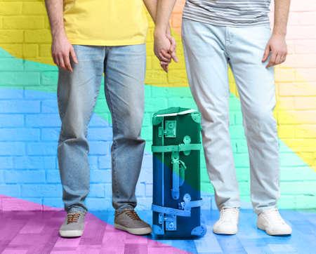 Homosexuelle Paare mit Koffer, Pässen und Karten auf Backsteinmauerhintergrund. Homosexuelle Ehe-Konzept