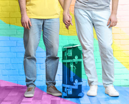 Gay couple with suitcase, passports and tickets on brick wall background. Homosexual marriage concept
