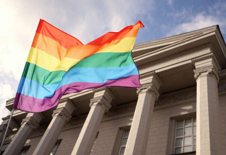 Waving gay flag and courthouse on background. LGBT right concept Archivio Fotografico