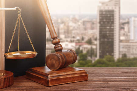 Judges gavel with book and scales on cityscape background, closeup. Concept of law
