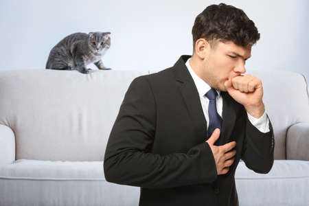 Ill man suffering from cough and pet on background. Concept of allergies to cats Stock Photo