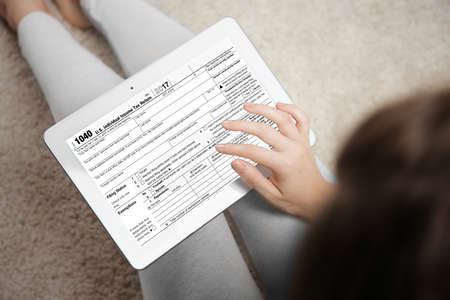 Woman using tablet for filling in individual income tax return form, closeup