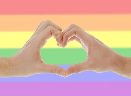 Gay couple making heart with hands and LGBT flag on background