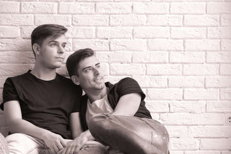 Gay couple on brick wall background