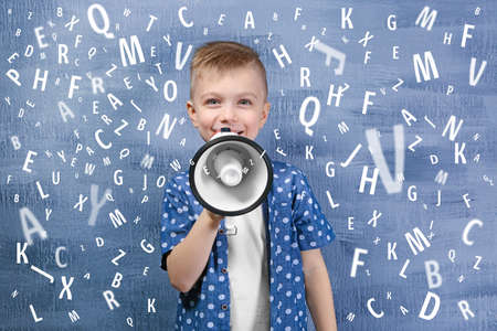 Little boy with megaphone and letters on blue background. Speech therapy concept Archivio Fotografico