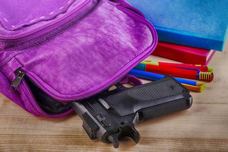 테이블, 근접 촬영 총을 가진 배낭. 학교 총격 사건 개념 스톡 콘텐츠