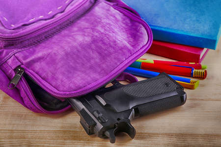 Backpack with gun on table, closeup. School shooting concept Reklamní fotografie - 92122304