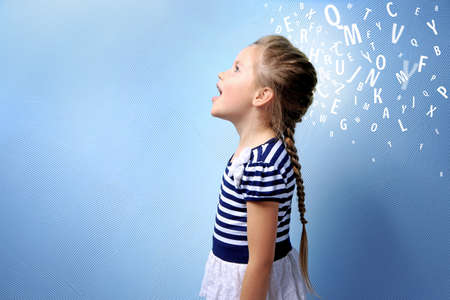Little girl and letters on blue background. Speech therapy concept Stock Photo