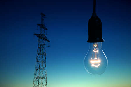 Electrical transmission tower and light bulb on sky background at night