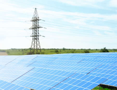 Solar panels and electrical transmission tower in field. Concept of eco friendly thechnology Stock Photo