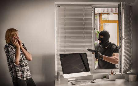 Terrorist aiming woman while she calling police. School shooting concept 版權商用圖片