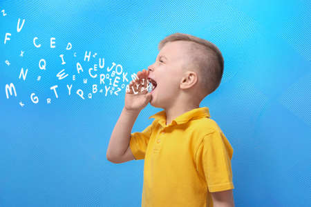 Little boy and letters on blue background. Speech therapy concept