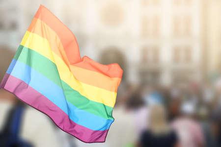 게이 플래그 및 배경에 사람들의 군중을 흔들며. LGBT 권리 및 퍼레이드의 개념 % 00