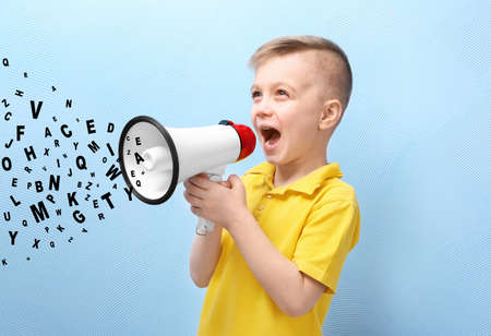 Little boy with megaphone and letters on blue background. Speech therapy concept Stock Photo