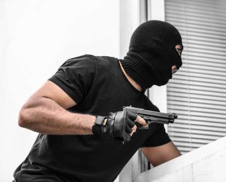 Terrorist with gun entering classroom through window. School shooting concept