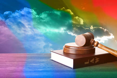 Judges gavel and book on wooden table against sky background. Gay rights concept