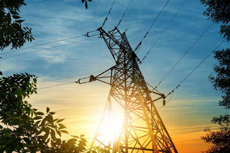 Electrical transmission tower on sky background at sunset