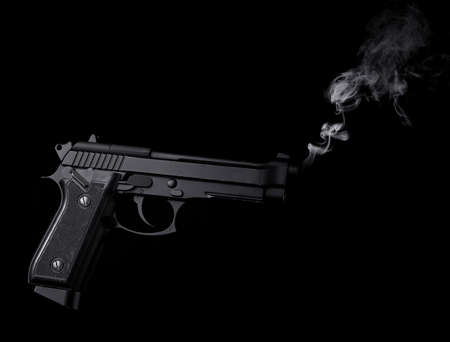 Smoking gun on black background Imagens