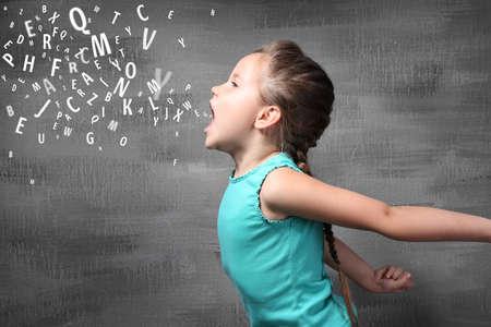 小さな女の子とグランジの背景に手紙。言語療法の概念