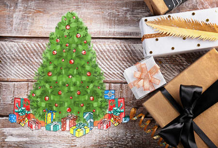 Gifts and drawing of Christmas tree on wooden background. Boxing day concept