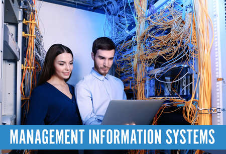 Concept of management information systems. Young engineers with laptop in server room