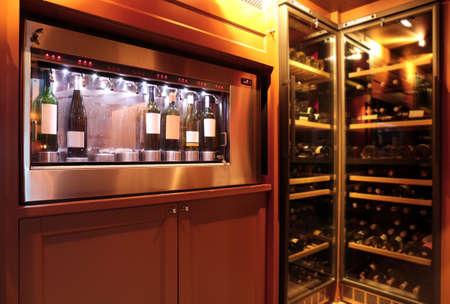 지하실에 와인 병이있는 디스펜서 및 냉장고