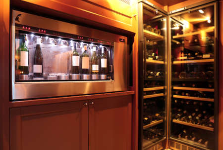 Dispenser and refrigerators with bottles of wine in cellar