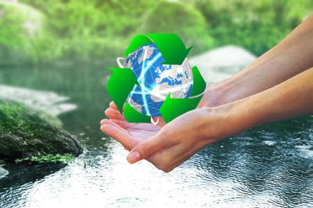 Mulher segurando globo e sinal de reciclagem sobre a água, closeup. Ecologia e conservação do meio ambiente