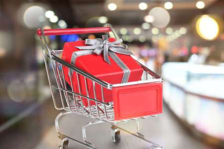 Market trolley with gift at shopping mall. Boxing day concept
