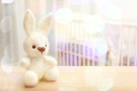Knitted toy bunny and blurred baby room on background. Holidays celebration concept