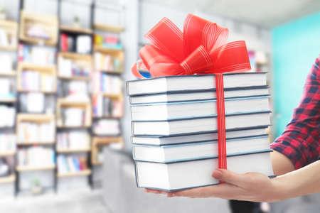 Kobieta trzyma książki z kokardą wstążki jako prezent w bibliotece