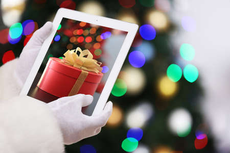 Santa shopping online for winter holidays and Christmas tree on background. Boxing day concept