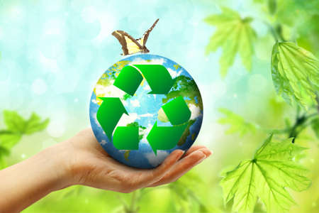Female hand holding globe and sign of recycling on blurred background. Ecology and environment conservation