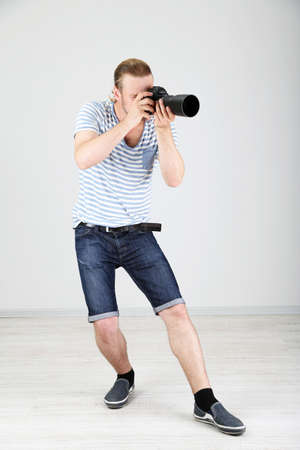 Handsome photographer with camera, on gray background Stock Photo