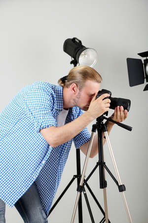 Handsome photographer with camera at working, on photo studio background