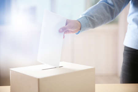 Woman putting document into ballot box