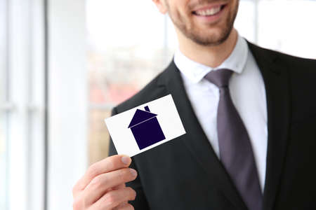Real estate agent holding business card with drawing of house on blurred background Stock Photo