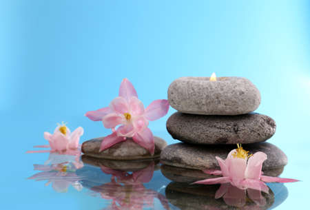 Stack of spa stones with flowers on blue background