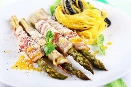 Dish of asparagus, bacon and pasta in plate on table, closeup