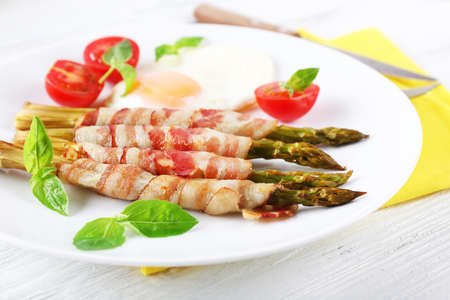 Dish of asparagus with bacon and egg in plate on table, closeup