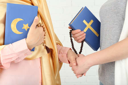 Two friends holding books with religions symbols Фото со стока