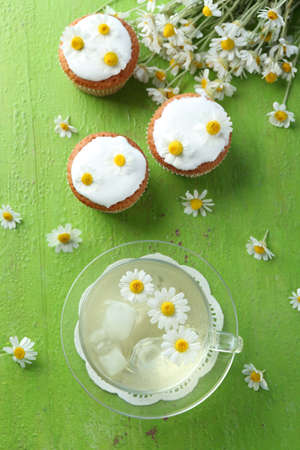 Cup of chamomile tea with chamomile flowers and tasty muffins on color wooden background Stock Photo