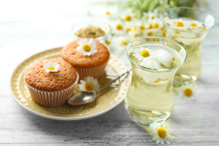 Glasses of chamomile tea with chamomile flowers and tasty muffins on color wooden background Stock Photo