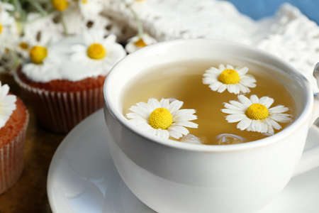 Cup of chamomile tea with chamomile flowers and tasty muffins on tray, on color wooden background Stock Photo