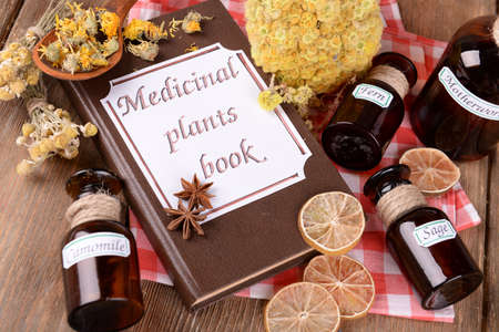 Het geneeskrachtige installatiesboek met droge kruiden en flessen op lijst sluit omhoog Stockfoto