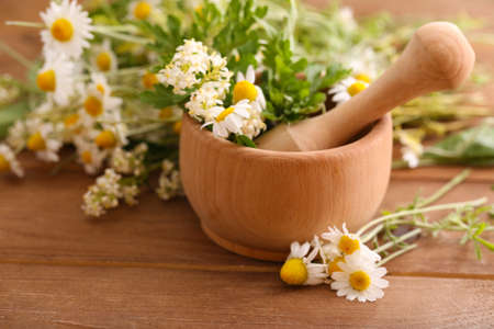 Herbs and flowers with mortar, on wooden table background Stock Photo