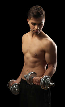 Muscle young man holding dumbbells on dark background Stock Photo