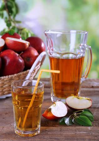 Glas Apfelsaft mit roten Äpfeln auf Holztisch auf unscharfen Hintergrund
