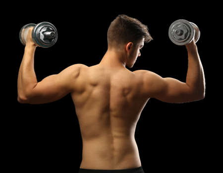 Muscle young man holding dumbbells on dark background Zdjęcie Seryjne